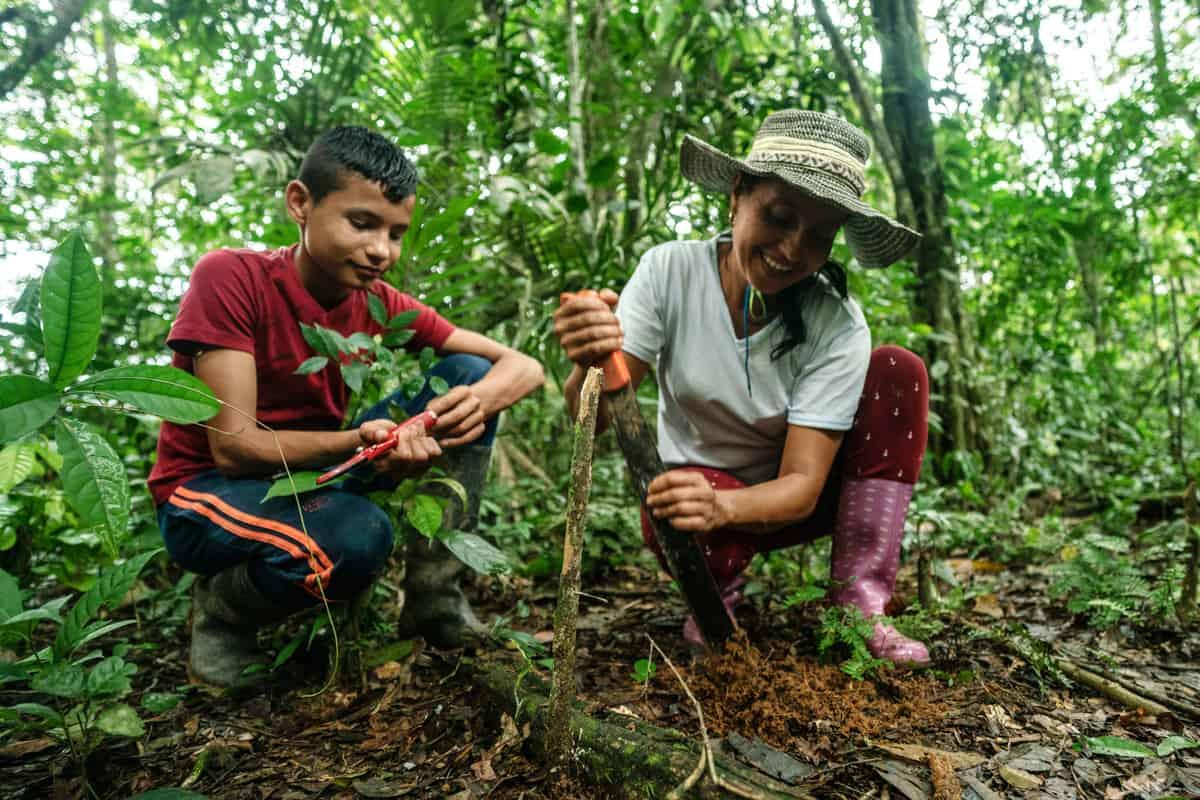 Landwirtin pflanzt gemeinsam mit ihrem Sohn einen neuen Baum als Teil eines Wiederaufforstungsprogramms