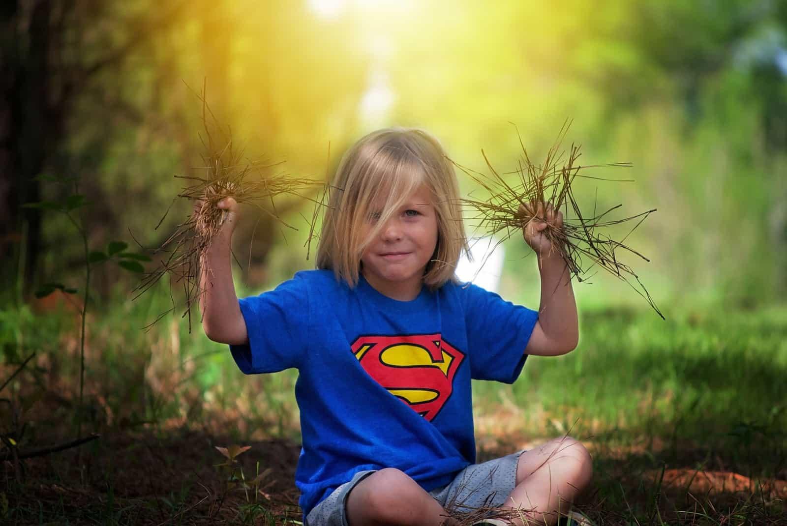 pflanzenarten-boden-bedeutsam-kind-mit-gras-in-den-haenden